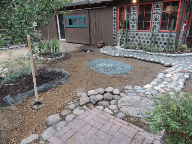 raked out with center marked with gravel for an outdoor oven